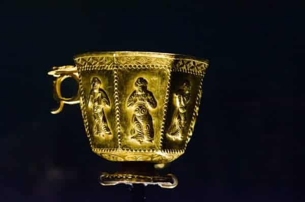 Gold octagonal cup with musicians and a dancer