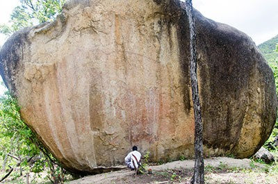 Elephant panel of rock art. The squatting human for a sense of scale and you can just barely see the outline of the top of the elephant.