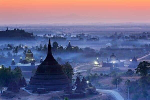 View from hazy sunset over silhouette Ratanabon Paya in Mrauk-U, Myanmar
