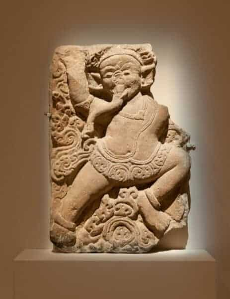 This wall relief is described as a dancer wearing an elephant mask. Does anyone know why this is identified as a dancer and not Ganesha?