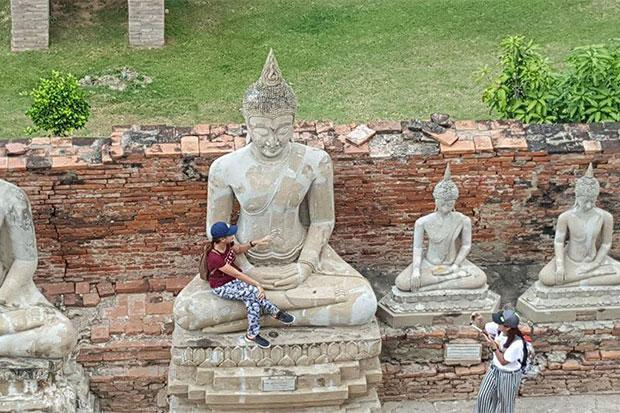 Woman sitting in lap of Buddha statue draws ire online