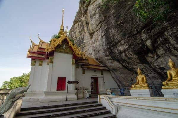 The cliff side of Wat Phraphuttachai. The rock art is located just to the right of the pavilion's entrance, behind the Buddha statues.
