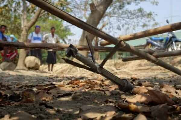 People look at an unexploded rocket in Mrauk U township in Rakhine State on March 16. Source: Frontier Myanmar 20190320